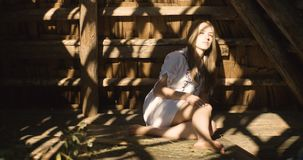 Young woman smiling in the sun rays on the hay. Wooden shed. 4K. stock footage