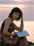 Young woman sitting at sunset stock photography