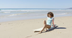 Young woman sitting on a surfboard Royalty Free Stock Images