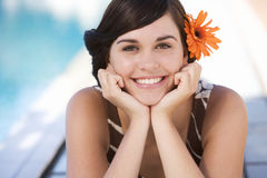 A young woman sitting by a swimming pool Stock Photography
