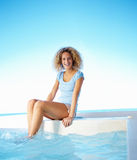 Young woman sitting by swimming pool and smiling Stock Photo