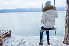 young woman sitting on a swing at a lake stock photo