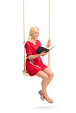Young woman sitting on a swing and reading a book. Vertical shot of a young woman in a red dress sitting on a swing and reading a book isolated on white royalty free stock photos