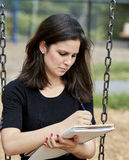 Young Woman sitting on Swing while Sketching on Sketch Pad Stock Image