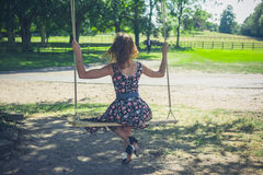 Young woman sitting on a swing Royalty Free Stock Image