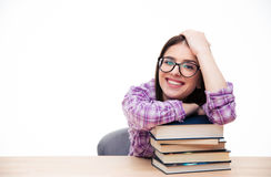 Young woman sitting at the table with book. Happy young woman sitting at the table with books and looking at camera Stock Images