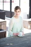 Young woman sitting at a table with a cup of coffe Royalty Free Stock Images