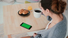 Young woman sitting at the table and drinking coffee in kitchen. Brunette girl uses smartphone, green screen. stock video footage