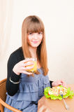 Young woman sitting at table drinking orange juice Royalty Free Stock Photography
