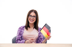 Young woman sitting at the table with German flag Stock Photo