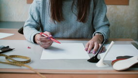 Young woman sitting at the table and holding pen on the white paper, preparing to draw sketch. Close-up. 4K stock video