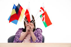 Young woman sitting at the table with international flags Stock Photography