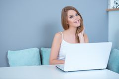 Young Woman Sitting at Table with Laptop Computer Stock Photos