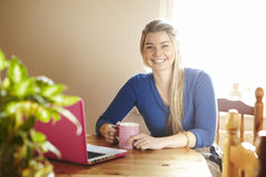 Young woman sitting at table with laptop smiling Royalty Free Stock Photography