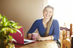 Young woman sitting at table with laptop smiling Stock Photography