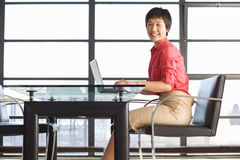 Young woman sitting at table with laptop, smiling, portrait, window in background Royalty Free Stock Photos