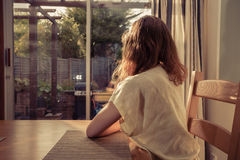 Young woman sitting at table and looking out the window Royalty Free Stock Photography