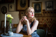 Young  woman sitting at a table in an old European cafe. Royalty Free Stock Images