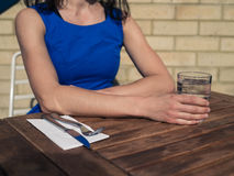 Young woman sitting at table outside restaurant Royalty Free Stock Photography