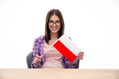 Young woman sitting at the table with Polish flag Royalty Free Stock Photos