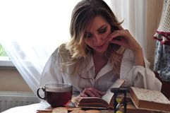 Young woman sitting by table and reading book. Young pretty woman sitting by wooden table and reading book Royalty Free Stock Image