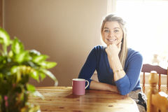 Young woman sitting at table smiling Stock Image