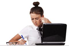 Young woman  sitting at a table taking notes Stock Images