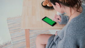 Young woman sitting at the table and touching the screen in kitchen. Girl uses smartphone, green screen during breakfast. Young woman sitting at the table and stock video footage