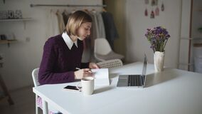 Young woman sitting at table and typing on keyboard notebook. Businesswoman. Two woman using laptop in home interior. Young woman sitting at table and typing on stock video