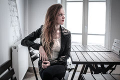 Young woman sitting at a table waiting royalty free stock images