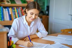 Young woman sitting at table in white shirt and signing papers, business concept stock photos