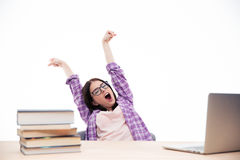Young woman sitting at the table and yawning Stock Photo