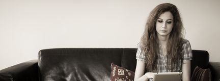 Young woman sitting with a tablet in a couch. Young woman sitting with a tablet i the center of a couch. Cover size Stock Photography