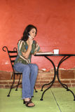 Young Woman Sitting and Talking on Cellphone Stock Images