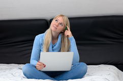Young woman sitting thinking on her bed stock photography