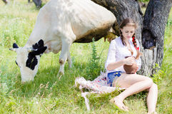 Young woman sitting tired near cows in countryside Royalty Free Stock Photos