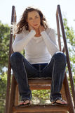 Young woman sitting top of ladder jeans white top Stock Photo