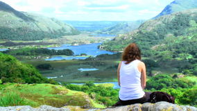 Young woman sitting on top of a mountain stock video