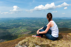 Young woman sitting on top of a mountain and looking at the land Stock Photo