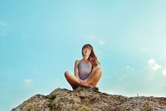 Young woman sitting on the top of mountain Stock Photo