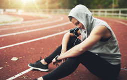 Young woman sitting on track field and preparing before running Royalty Free Stock Images