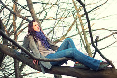 Young woman sitting on tree in the forest Stock Photos