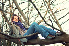 Young woman sitting on tree in the forest Stock Photography