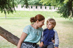 Young woman sitting on tree with her little son  and speaking Royalty Free Stock Image