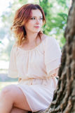 Young woman sitting on a tree Royalty Free Stock Images