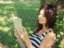 Young woman sitting on a tree. Read leaning against a tree Stock Photo