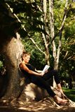 Young woman sitting on a tree and reading Royalty Free Stock Photography