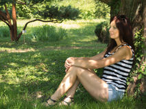 Young woman sitting on a tree. Thin woman with sexy legs sitting on a green park Stock Photos