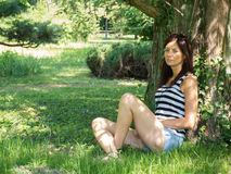 Young woman sitting on a tree. Thin woman with short sitting on a green park Royalty Free Stock Photos