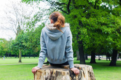 Young woman sitting on tree trunk in park Royalty Free Stock Image